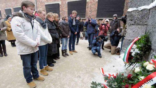 Sylvia Löhrmann und Jugendliche stehen an der Todesmauer im Konzentrationslager Auschwitz