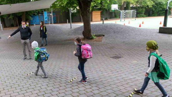 Kinder gehen auf Abstand über das Schulgelände
