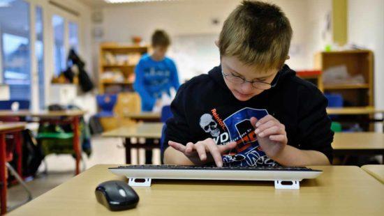 Junge sitzt an Tastatur in Förderschule