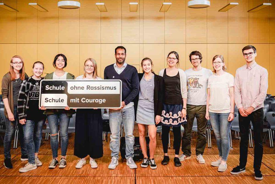 Jugendliche mit Schild, auf dem steht Schule ohne Rassismus - Schule mit Courage