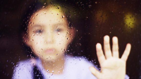 Mädchen hinter einem verregnetem Fenster