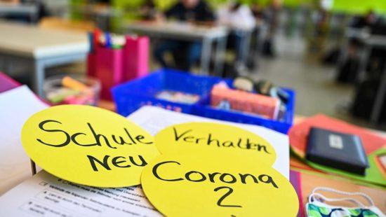 Schüler der Abschlussklasse sitzen in der Achtalschule im Klassenzimmer, während auf dem Lehrerpult drei kreisrunde Papierschilder mit der Aufschrift Schule neu, Verhalten und Corona liegen.