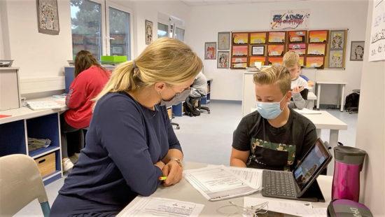 Schüler und Lehrerin mit Maske