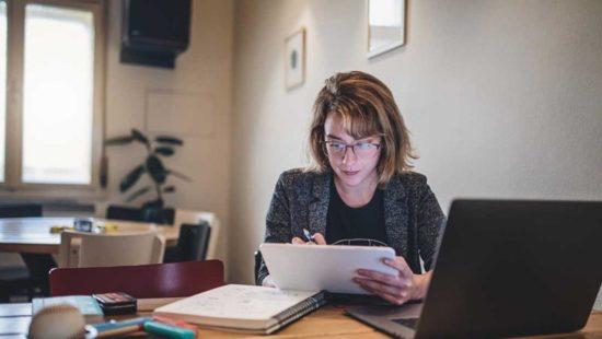 Eine Frau sitz mit dem Tablet am Schreibtisch