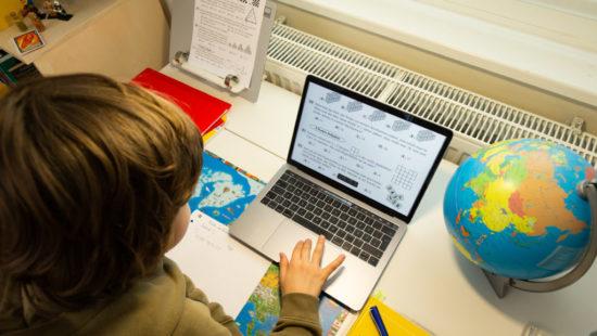 Ein Schüler sitzt zu Hause vor dem Laptop