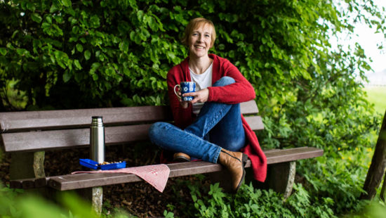 Martina Schmidt sitzt auf einer Bank mit einer Tasse in der Hand