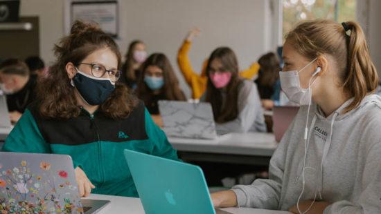 Schülerinnen im Klassenraum mit Maske und Laptops