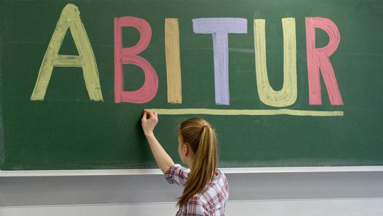 Abiturprüfungen Jugendliche unterstreicht das Wort Abitur auf Tafel