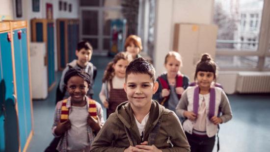 Eine Gruppe Grundschulkinder steht auf dem Schulflur und lächelt in die Kamera
