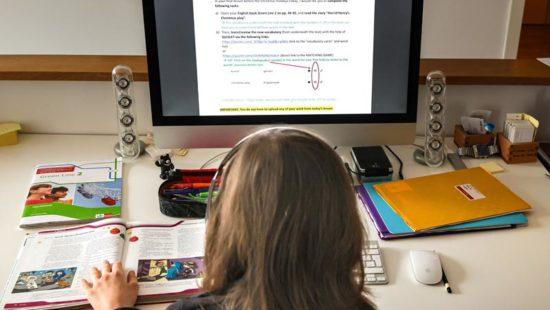 ein Kind sitzt zu Hause vor dem Bildschirm und macht Hausaufgaben