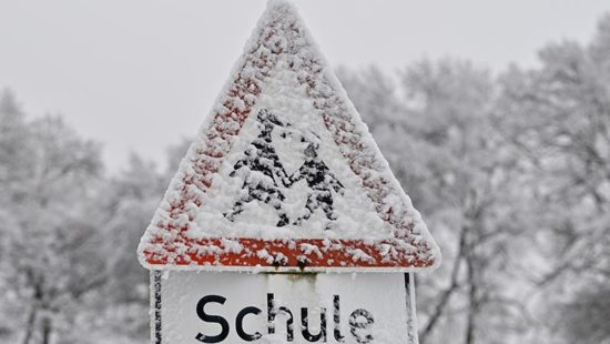 verschneites Straßenschild mit Aufschrift Schule