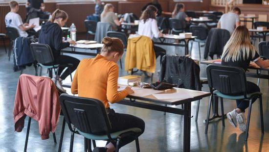 AbiturJugendliche sitzen an Tischen bei den Prüfungen
