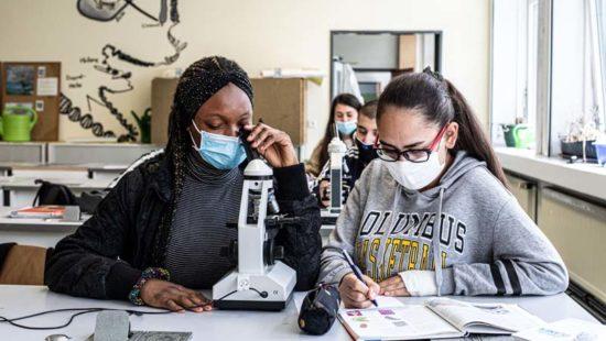 Zwei Schülerinnen sitzen am Mikroskop