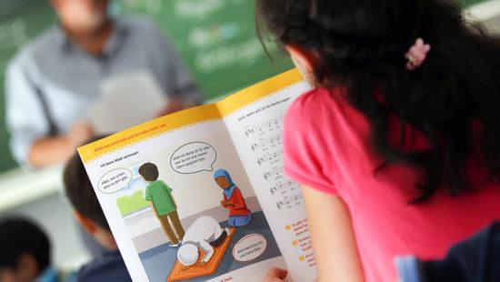 ein Mädchen schaut in ein Lehrbuch für Iden islamischen Religionsunterricht