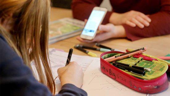 Pandemie-Schooling Kind beim Schreiben, Mutter mit Handy