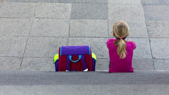 sexueller Kindesmissbrauch Mädchen und Schulranzen von hinten