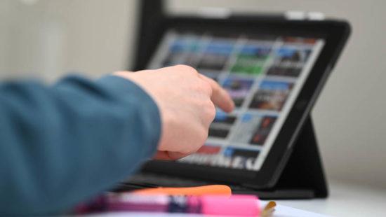 Schüler zeigt auf ein Tablet mit der Lernplattform Moodle